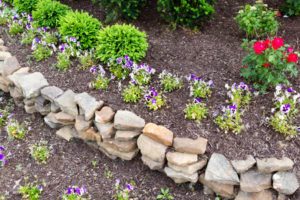40546814 - natural rock retaining wall in a garden with rough rocks and stones arranged in a curve for a formal raised bed of flowering plants in a garden landscaping concept